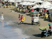 إقبال على شاطئ بورسعيد وهدوء فى الأمواج بالعوامات الألوان.. لايف وصور