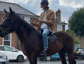 شاب بريطانى يسخر من أزمة الوقود بجولة على ظهر حصانه بين السيارات المعطلة.. فيديو