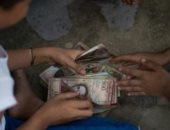 الأطفال يلعبون بأوراق عملة البوليفار بعد فقدان قيمتها فى فنزويلا.. فيديو