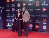 محمد فراج يقبل يد زوجته بسنت شوقى على السجادة الحمراء بمهرجان الجونة