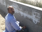 بالصور.. فنان من المنيا يتحدى الإعاقة بالرسم على الطرق السريعة