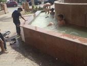 بالصور.. أطفال السويس يهربون إلى النافورات بسبب ارتفاع درجات الحرارة