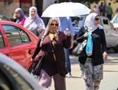 المصريون يهربون من الحر بالشماسى والكاب والشنط البلاستيك