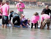كلب يتحدى إعاقة صديقتيه ويساعدهما على ركوب الأمواج